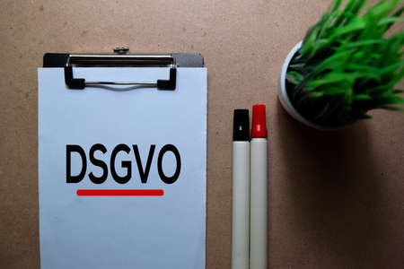 DSGVO write on a paperwork. Isolated on Wooden Table Stockfoto