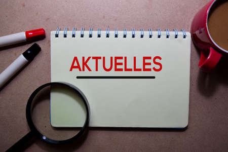 Aktuelles write on a book. for news and update. Isolated on Wooden Table