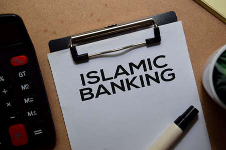 Islamic Banking write on a paperwork. Isolated on Wooden Table