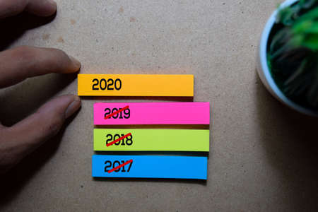 Man Pulling 2020 sticky note on wooden table background. Happy New Year Concept