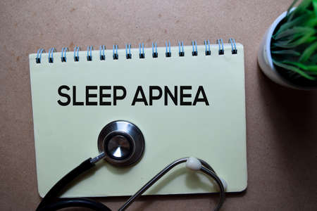 Sleep Apnea write on a book with stethoscope. Isolated on wooden table Stockfoto