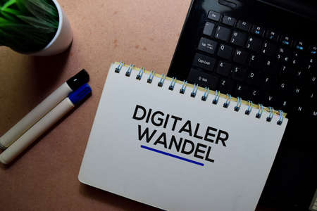Digitaler Wandel write on a book and laptop. Isolated on wooden table Stockfoto