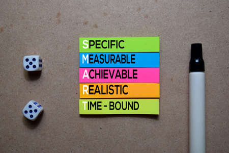 SMART - Specific, Measurable, Achievable, Realistic, And Time-Bound write on Sticky note. Isolated on wooden table