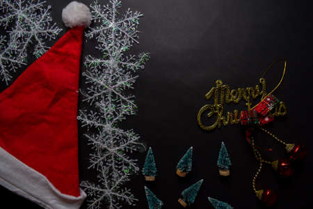 Santa Claus red hat, merry christmas text and Decorative Christmas gifts isolated on black background