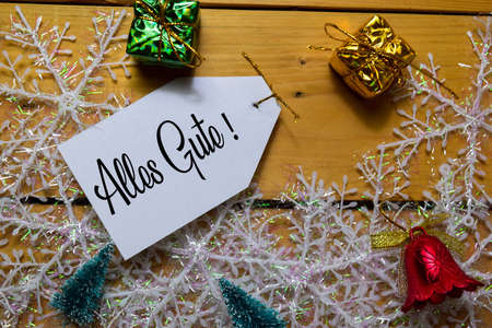 Alles Gule write on label with wooden backgroud. It means Best Wishes. Frame of Christmas Decoration.
