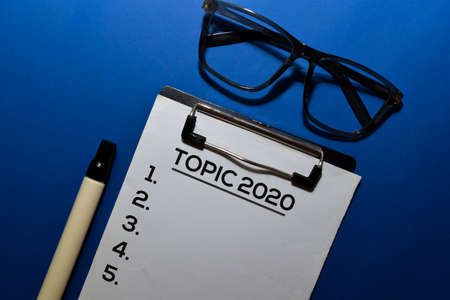 Topic 2020 write on document isolated blue background.