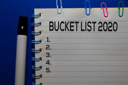 Bucket List 2020 write on book isolated on wooden table. Medical or Finance concept