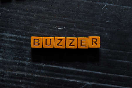 Buzzer on wooden cubes. On table background Фото со стока