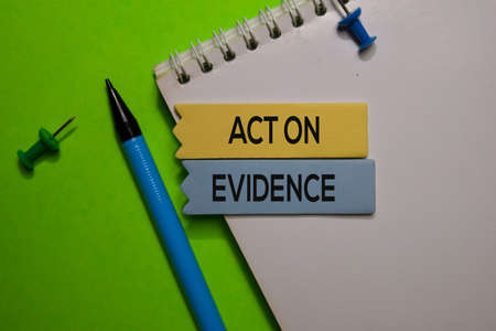 Act On Evidence write on sticky note isolated on Office Desk.