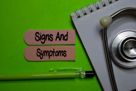 Signs And Symptoms write on sticky note isolated on Office Desk. Healthcare or Medical Concept Stockfoto