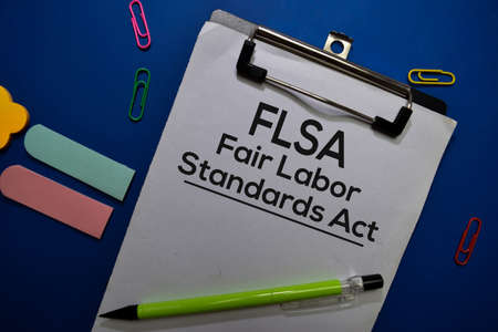 FSLA - Fair Labor Standards Act write on a paperwork isolated on Office Desk