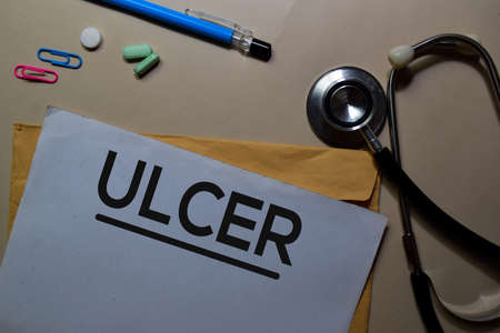 Ulcer text on document above brown envelope and stethoscope. Healthcare or medical concept