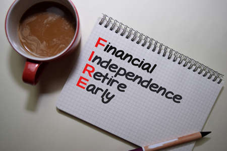 Financial Indipendence Retire Early write on a book isolated on Office Desk.