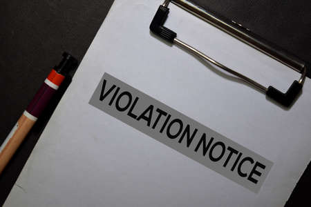 Violation Notice write on a paperwork isolated on black table.