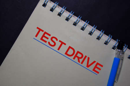 Test Drive write on a book isolated on black table. Stockfoto