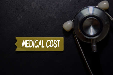 Medical Cost write on sticky note isolated on black table.