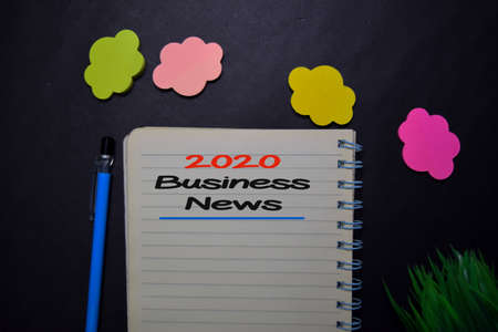 2020 Business News write on a book isolated on black table.