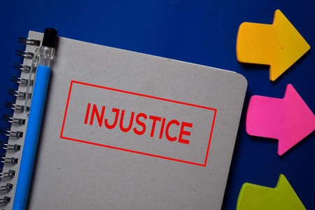Injustice write on a book isolated on blue background.