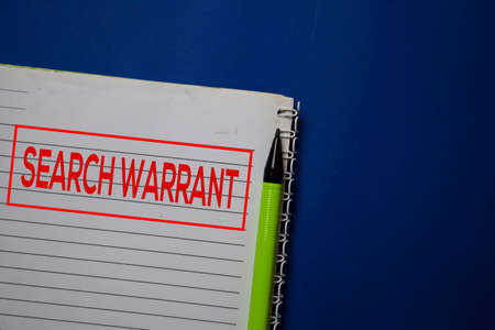 Search Warrant write on a book isolated on blue background.