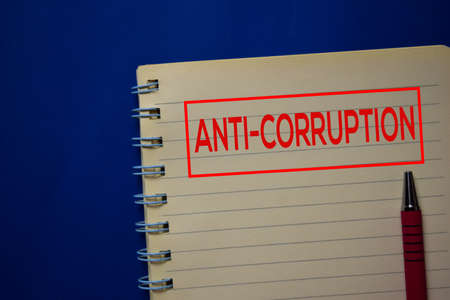Anti-Corruption write on a book isolated on blue background.