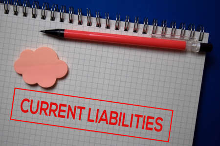 Current Liabilities write on a book isolated on blue background.