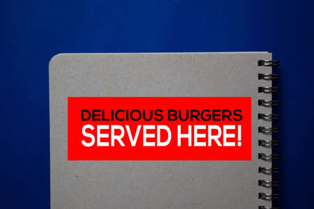Delicious Burgers Served Here! write on a book isolated on blue background. Stockfoto