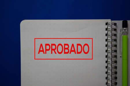 Aprobado write on a book spanish language isolated on blue background.