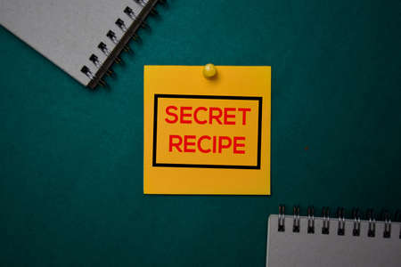 Secret Recipe write on a sticky note isolated on green background.