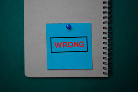 Wrong write on a sticky note isolated on green background. Stockfoto