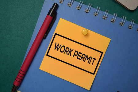 Work Permit write on a sticky note isolated on green background.
