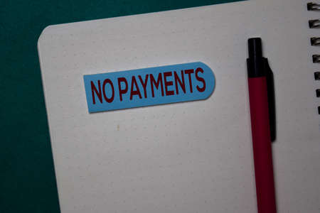 No Payments write on a sticky note isolated on green background. Stockfoto
