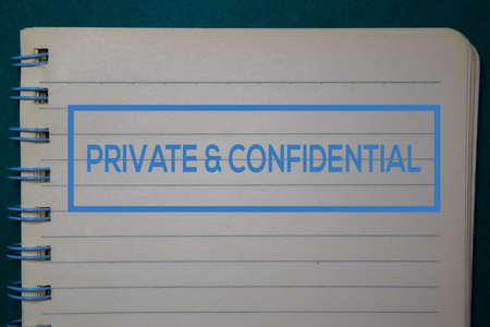 Private & Confidential write on a book isolated on green background.