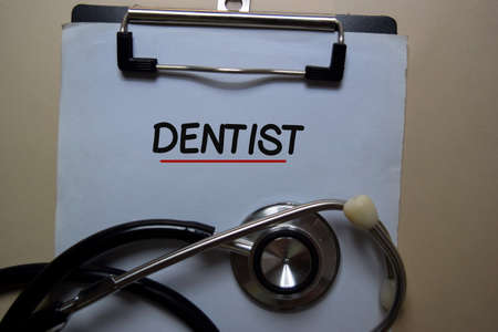 Denstist write on a paperwork and stethoscope isolated on office desk. medical or healthcare concept