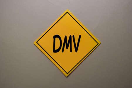 DMV write on a sticky note isolated on office desk.