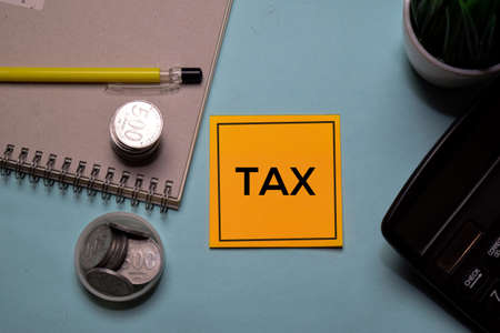 Tax write on a sticky note isolated on office desk.