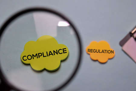 Compliance and Regulation write on a sticky note isolated on office desk.