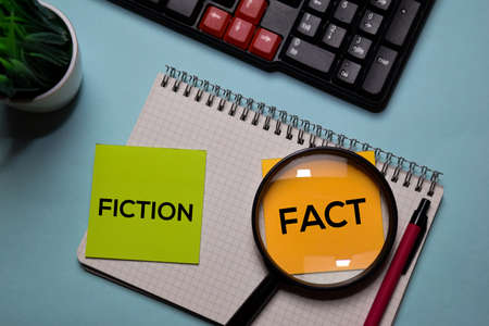 Fiction and Fact write on a sticky note isolated on office desk.