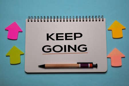 Keep Going write on a book isolated on office desk. Christian faith concept