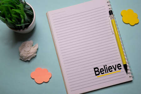 Believe write on a book isolated on office desk. Christian faith concept