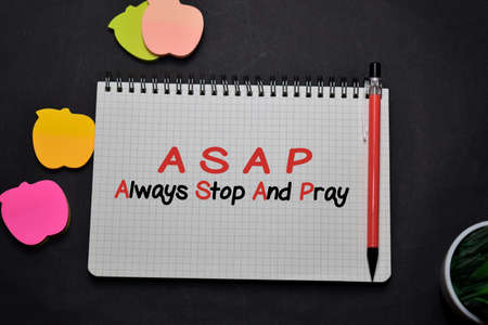 ASAP - Always Stop And Pray write on a book isolated on office desk. Christian faith concept