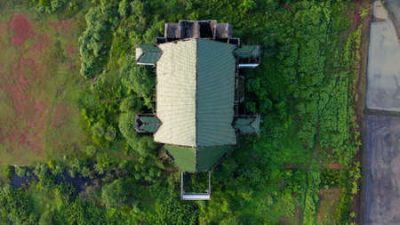 Aerial, Drone Shot, above on abandoned farmhouse surrounded by paddy rice field, in the city of Bekasi, on a sunny, summer day, in Indonesia.