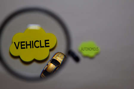 Vehicle or Autonomous write on a sticky note isolated on office desk. Selective focus on Vehicle text Reklamní fotografie