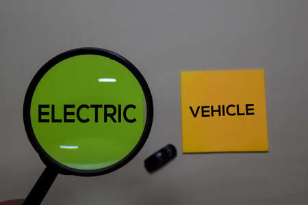 Electric or Vehicle write on a sticky note isolated on office desk.