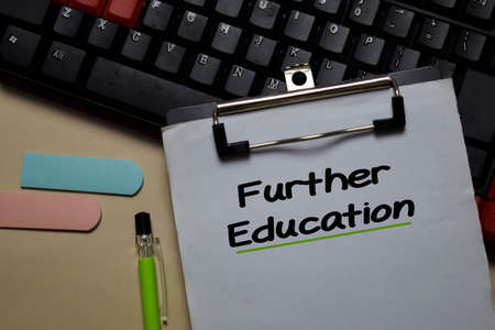 Further Education write on a paperwork isolated on Office Desk