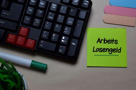 Arbeitslosengeld write on a sticky note isolated on office desk. German Language it means Unemployment Benefit Reklamní fotografie