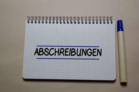 Abschreibungen write on a book isolated on office desk. German Language it means Depreciation