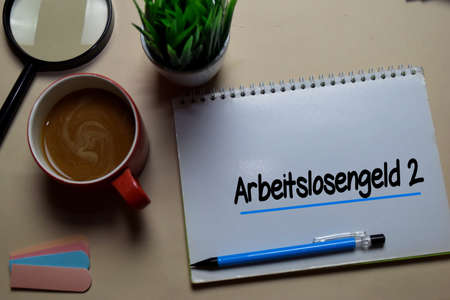 Arbeitslosengeld 2 write on a book isolated on office desk. German Language it means Unemployment Benefit