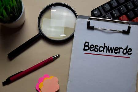 Beschwerde write on a paperwork isolated on office desk. German Language it means Complaint Reklamní fotografie