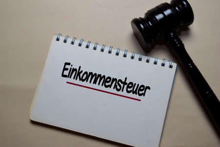 Einkommensteuer write on a paperwork with gavel isolated on Office Desk. German Language it means Income Tax