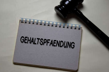 Gehaltspfaendung write on a book with gavel isolated on Office Desk. German Language it means Salary Garnishment